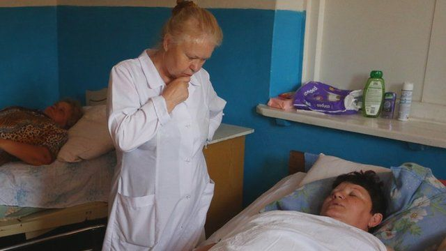 A nurse attends a woman after she was injured by shelling between Ukrainian forces and pro-Russian separatists.