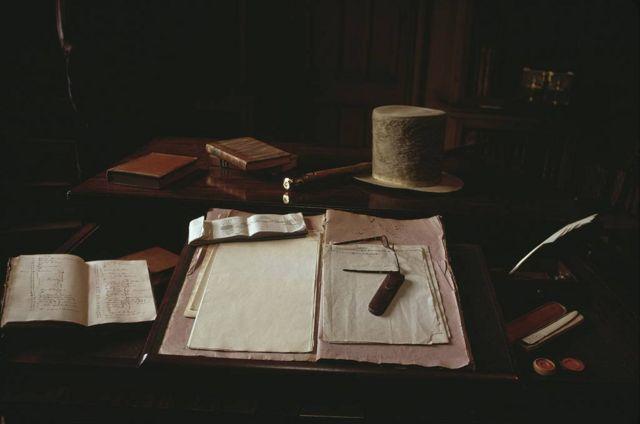 Gafas, un sombrero, una pluma y papel de escribir sobre el escritorio en la casa del novelista, dramaturgo y poeta escocés