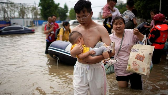 A man holding a baby wades through a flooded road following heavy rainfall in Zhengzhou, Henan province, China July 22, 2021