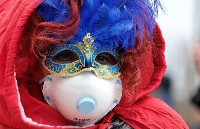 """Masked carnival reveller wears protective face mask at Venice Carnival, which the last two days of, as well as Sunday night""""s festivities, have been cancelled because of an outbreak of coronavirus, in Venice, Italy February 23, 2020"""