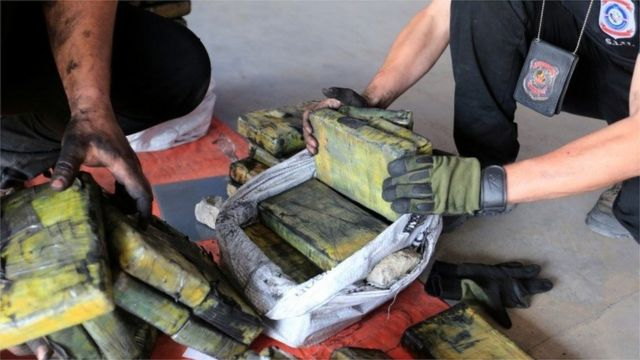 Police officers check packages of cocaine that were hidden in a shipment of six charcoal containers that were to be shipped to Israel after being seized by an anti-narcotics unit in the Terport de Villeta port in Villeta near Asuncion, Paraguay, October 20, 2020.