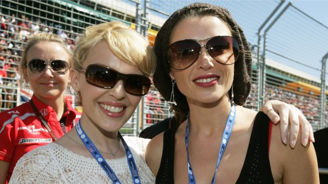 Singers Kylie Minogue (L) and sister Dannii Minogue pose on the grid at the Australian Formula One Grand Prix at the Albert Park Circuit on 18 March 2007 in Melbourne, Australia