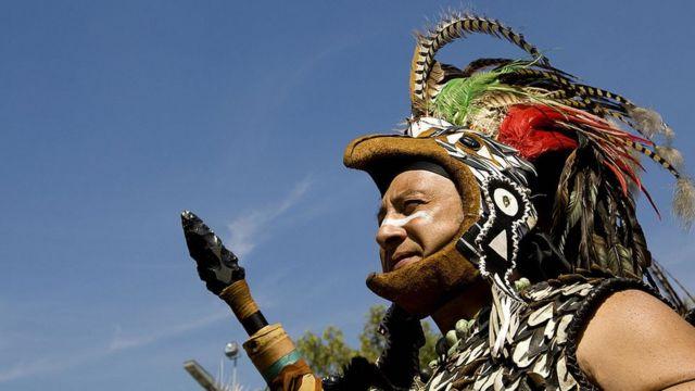 Un hombre representa un guerrero azteca