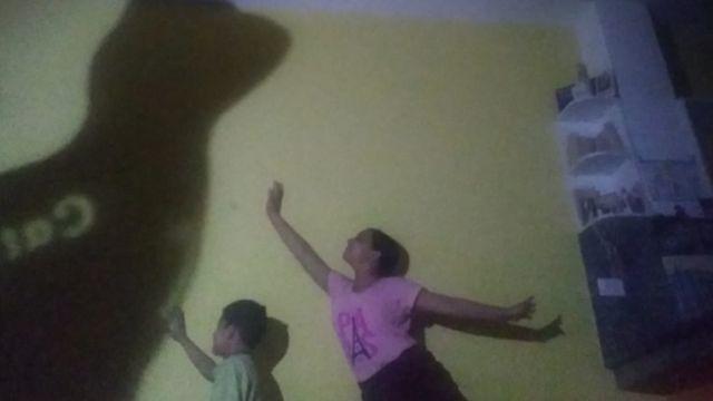 Valeria con hermano jugando con al sombra de su gata.