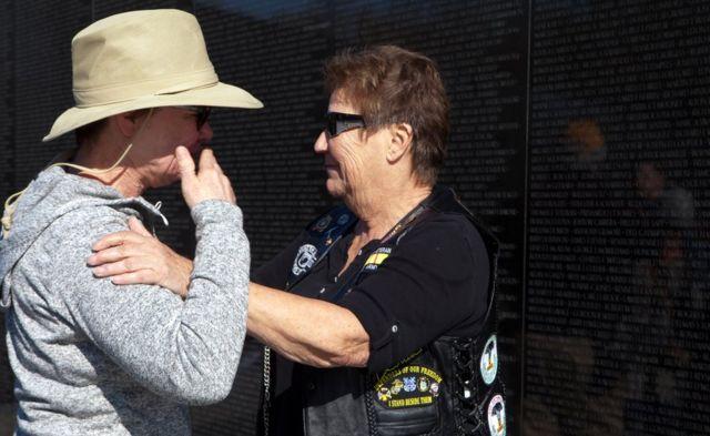 """Starnes consuela a una visitante en el Vietnam Veterans Memorial, conocido como """"la Pared de Vietnam"""", en Washington DC, Estados Unidos."""
