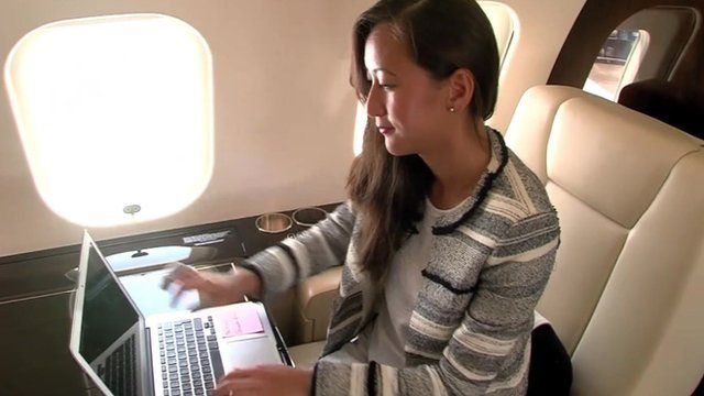 Leish Chi with laptop on aircraft