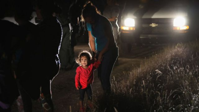 A pequena menina, agora calma, de mãos dadas com a mãe