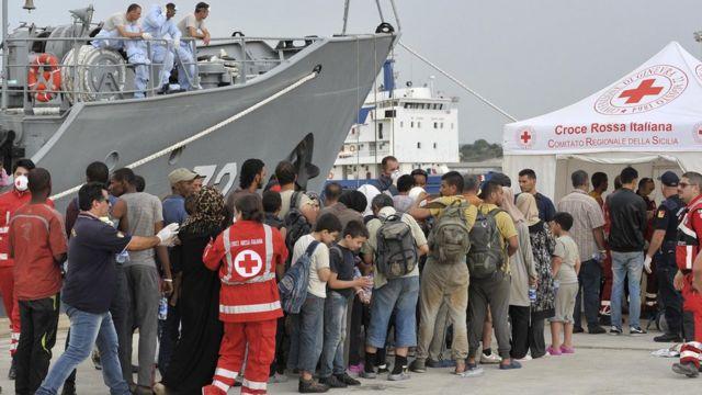 クロアチアの海岸警備隊の船から下船し赤十字の臨時施設に集まる移民(イタリア・シチリア、8月16日)