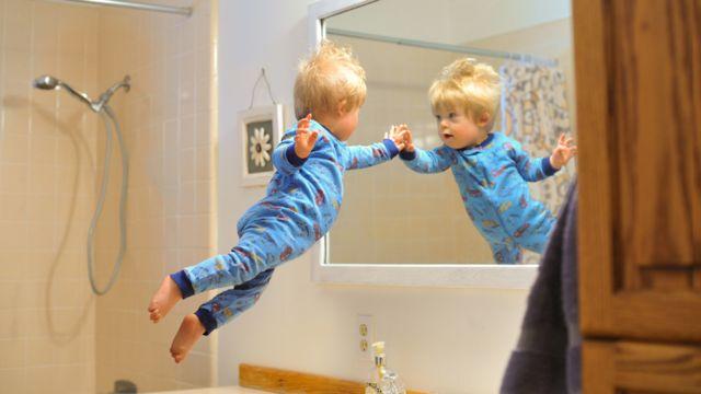 Wil volando en sus piyamas mirando su imagen en el espejo del baño