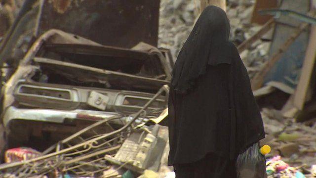 Woman walks among rubble in Aden