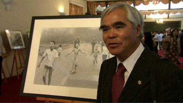 Nick Út đứng cạnh bức ảnh Em bé Napalm tại triển lãm ảnh AP ở Hà Nội