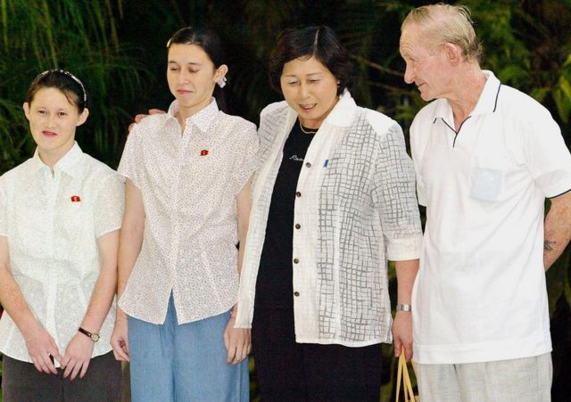 The Jenkins family smile awkwardly for photographers in Indonesia on 11 July 2004.