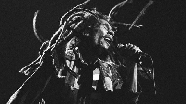 Bob Marley en pleno concierto. Tiene los ojos cerrados y cabellos rastas revueltos.