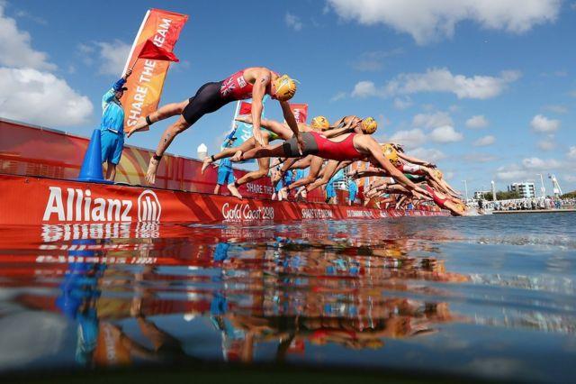 خواتین کے ٹرائیتھیلون مقابلوں میں ایتھلیٹس پانی میں ڈائیو کرتے ہوئے۔