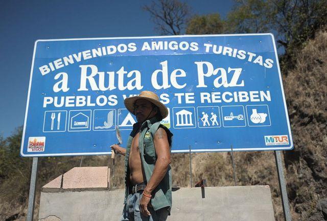 """Un trabajador frente a un cartel de la """"ruta de la paz"""" en Osicala, en Morazán."""