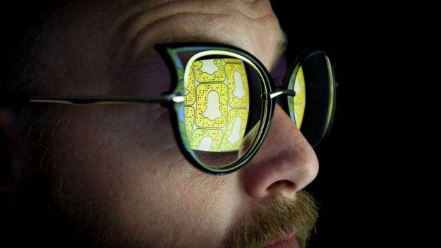 Hombre con bigote y gafas de sol en las que se refleja el logo de Snapchat