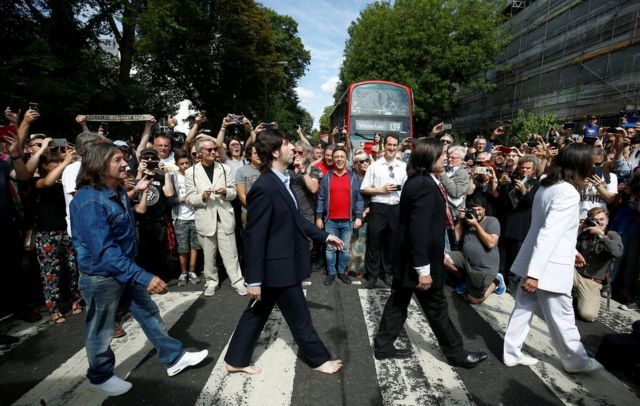 People gather round a pedestrian crossing in London