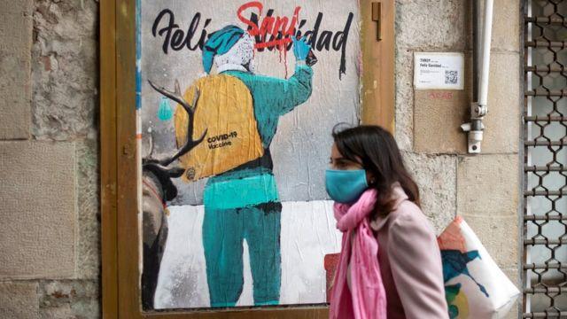 Una mujer más allá de la nueva creación del artista callejero italiano TV Boy que representa a Santa Claus llevando la vacuna Govt-19 en su saco