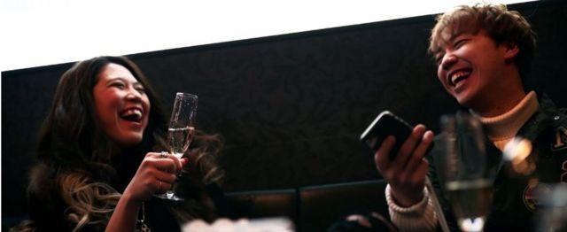 businesswoman Aki Nitta (L) drinks champagne