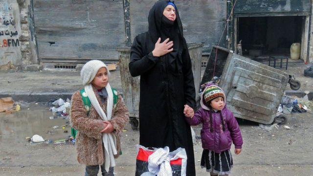 सीरियाई महिला अपने बच्चों के साथ.