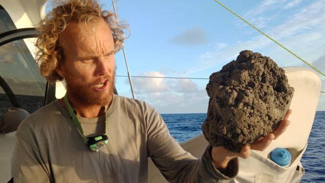 Michael Hoult sostiene una gran roca de pómez