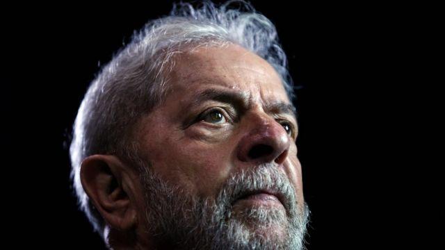 Lula de perfil, fotografado de cima pra baixo, com olhar sério e fundo preto