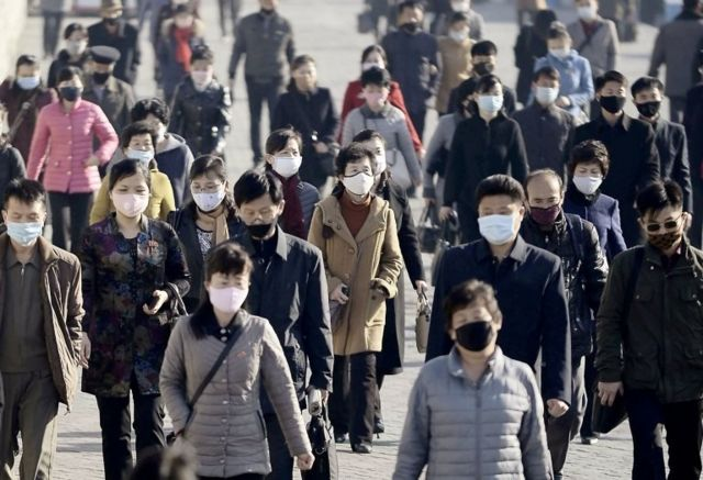 People wearing protective face masks commute amid concerns over the new coronavirus disease (COVID-19) in Pyongyang, North Korea March 30, 2020