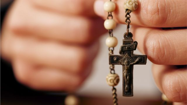 Manos sosteniendo un rosario con crucifijo
