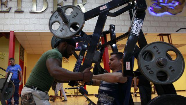 Homens praticando musculação em academia