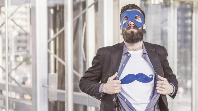Le Hipster Superhero : un jeune homme (style hispter) avec une grosse boucle d'oreille et une barbe pleine essaie d'imiter un super héros portant un t-shirt avec une grosse moustache imprimée dessus.