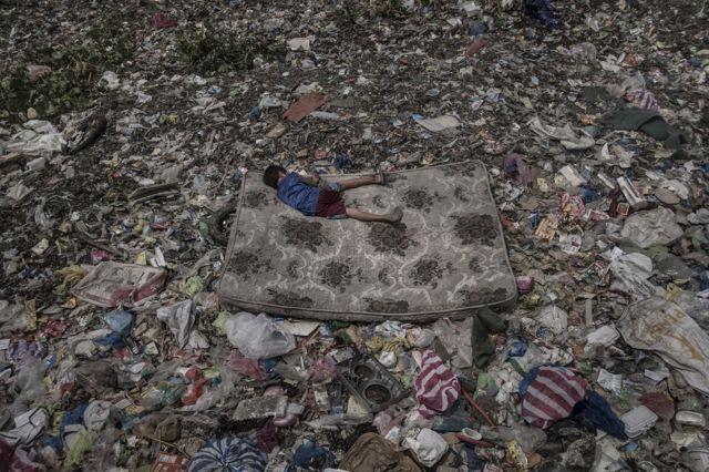 Seorang bocah merebahkan diri di atas kasur di tengah gunungan sampah