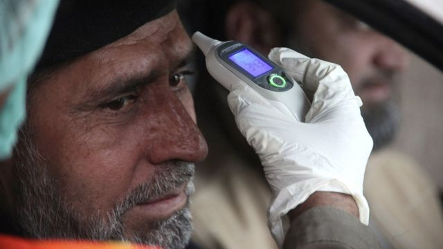 Un hombre con un termómetro electrónico en la frente