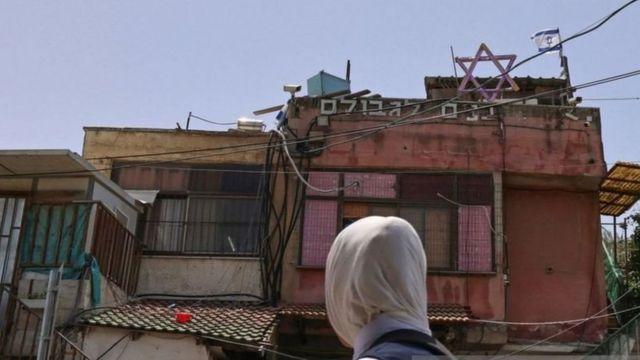 فتاة أمام منزل عليه لافتات إسرائيلية
