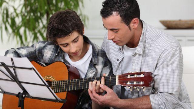 A Bark guitar teacher helping a boy to learn the instrument