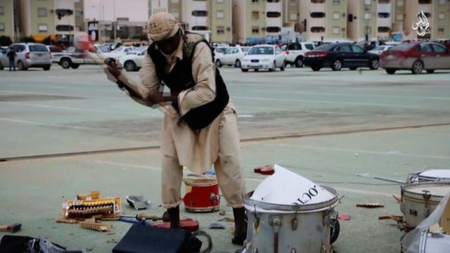A member of Islamic State's religious police smashes up a drum-kit in the streets of Sirte with a sledgehammer, since it is deemed an un-Islamic musical instrument.