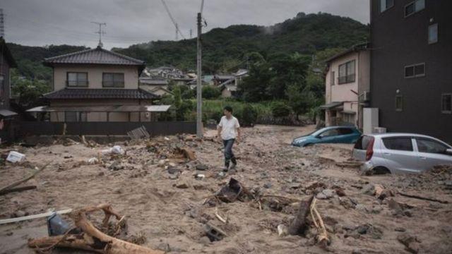 Homem caminha em área que sofreu com enchente