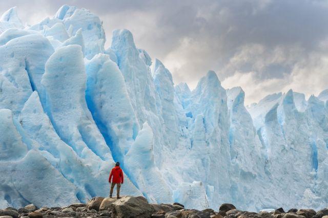 คนยืนอยู่บนธารน้ำแข็งในอาร์เจนตินา