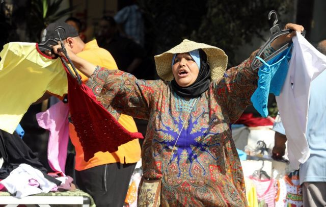 A woman sells clothes at a street market in Cairo