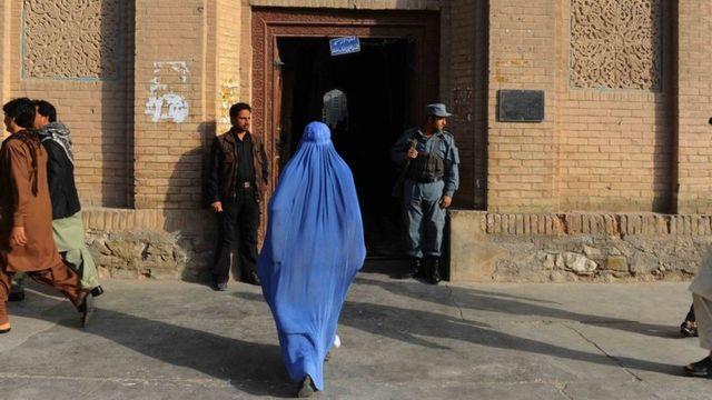 Uma mulher entra em um edifício em Herat