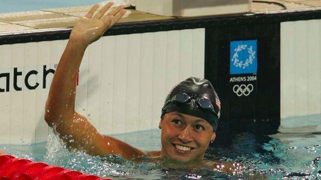 Tara Kirk Sell waving at one end of a pool