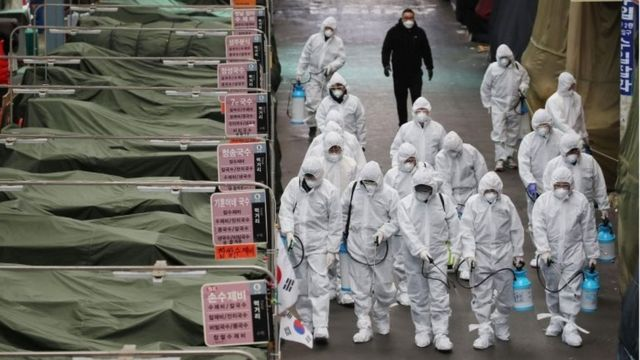 Market workers wearing protective gear spray disinfectant at a market in the southeastern city of Daegu on February 23, 2020