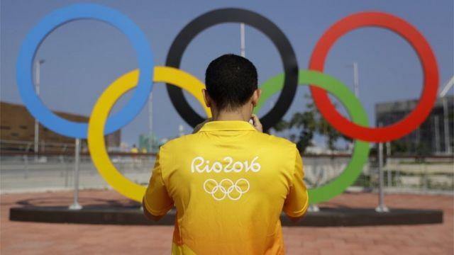 Homem com camiseta do RIo2016 tira foto diante de arcos olímpicos