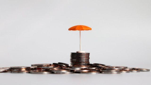 Um guarda-chuva laranja em uma pilha de moedas