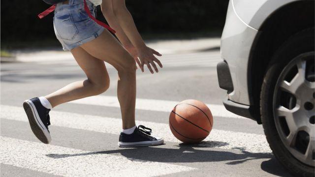 Баскетбольный мяч под колесами автомобиля