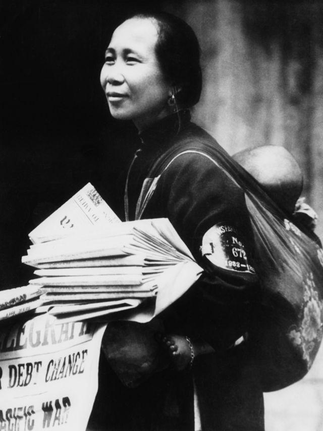 一名背着婴儿的妇女在香港街头卖报(1943年)