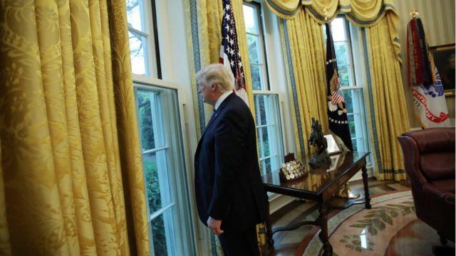 O presidente americano Donald Trump olha pela janela da Casa Branca