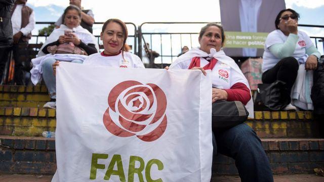 Dos mujeres sostienen una pancarta con el logo de la FARC.