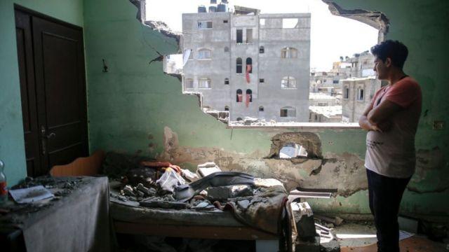 Um homem palestino inspeciona os danos em seu quarto após ataques aéreos israelenses em seu bairro no campo de refugiados de Jabalia, Faixa de Gaza do Norte em 20 de maio de 2021
