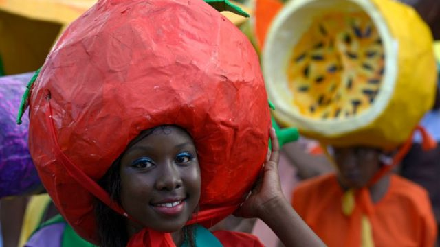 Girl wey carry big red headdress for head for Seychelles Carnival.