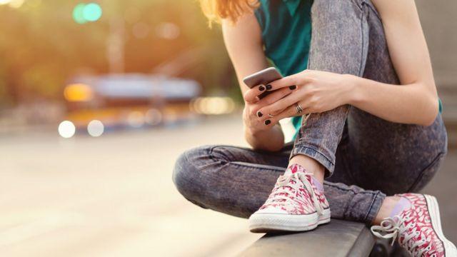 Adolescente usando teléfono